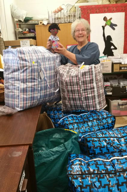 Georgia Efford, director Uthando project delighted with the progress of the packing of Dolls for shipment.