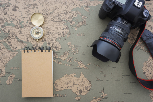 travel-composition-with-compass-camera-and-notebook_23-2147607770